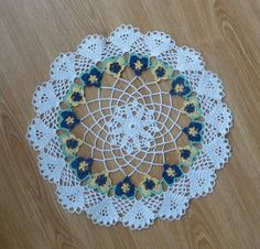 This pattern is for a crochet lacy doily that incorporates a band of pansies in the design.