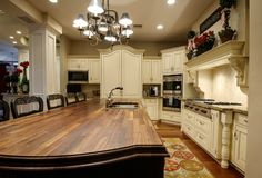 Incredible wood-topped island in white luxury kitchen.  This island is like one massive chopping block.