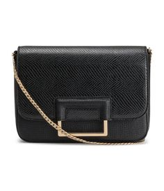 Black/gold-colored. Shoulder bag in grained imitation leather with metal chain…