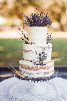 Ramitas de trigo y lavanda adornan este pastel semi-desnudo para bodas rústicas chic de Jonson's Custom Cakes & More.