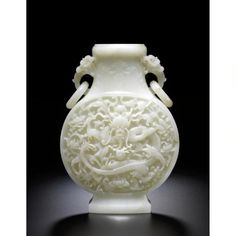 A finely carved white jade 'Dragon' moonflask. Qing dynasty, Qianlong period, of flattened globular form, well carved on each side with a frontal five-clawed dragon, its sinuous body wrapped around a 'flaming pearl', leaping amongst lotus scrolls and bajixiang, the waisted neck adorned with stylised floral and foliate designs, flanked by a pair of dragon ring handles, the lustrous stone of an even white tone with natural inclusions.