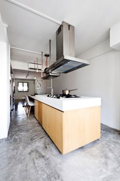 """""""The conjoined dining table and island unit - complete with counter space, sink and hob - saves space in the kitchen. The sink and hob are slightly raised to demarcate the cooking and dining zones."""""""