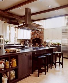 This kitchen was built for a professional chef. The highlights for me are the brick stove with the copper pots and pans, the beams along the ceiling, all the natural light, and that amazing island.