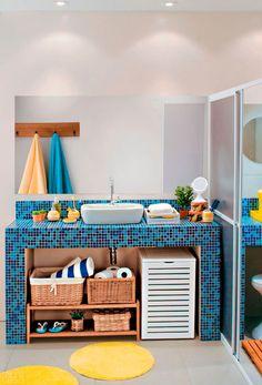 Projetos dos arquitetos Saulo Szabó e Fernando Oliveira, este banheiro tem duas generosas bancadas de alvenaria: a tradicional, da pia, e uma dentro do boxe. A mistura de acabamentos inclui porcelanato e pastilhas de vidro. A decoração vem para aquecer com toques de madeira e fibra natural.