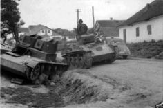 Toldi I light tank passes by a knocked out Soviet T-26 in 1941