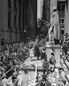 VE Day In New York City: Confetti and streamers flying down from office bldgs. as people celebrating news of the end of war in Europe, jam Wall Street in front of the statue of George Washington on the steps of Federal Hall across from,the the New York Stock Exchange, May 7, 1945.