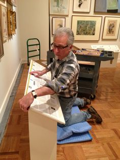 """'A Peek Behind the Curtain' ~ Jim Via installing wall labels for """"It Came From the Vault"""""""