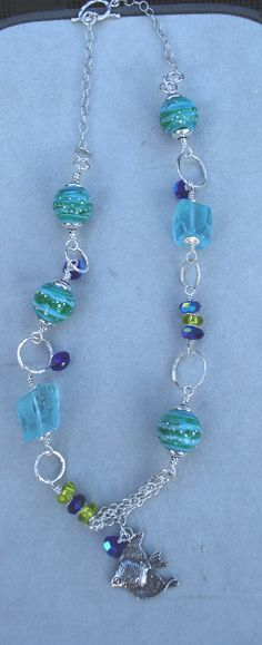 3rd reveal - Bright blue crystals from my partner Regina Wood, along with my Lampwork Beads, tumbled quartz and my handmade fused silver circles.  A sterling silver fish dangles from the center.