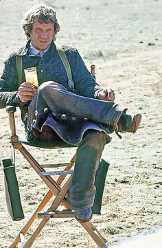 A leather-chapped McQueen sits in the director's chair on the set of Tom Horn with a glass of iced down Old Milwaukee beer, his favorite beverage. – By Barbara Minty McQueen –