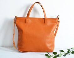 Simple and roomy tote bag made from high quality pebbled leather. This large tote bag is suitable for carrying everything in your everyday life. Spacious interior provides room for all the daily essentials and more. It has a top zip closure. The bottom of the bag is lined with leather on the inside for extra support.  * Highest quality Italian leather * Includes interior zipped pocket + 2 open pockets, key chain * Adjustable and removable shoulder strap (to be worn on the shoulder or…