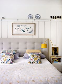 Gray headboard, patterned pillows, yellow reading light, and shelf above the bed. <3