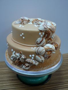 beautiful beach / ocean themed wedding cake with brown and white shells. I am so making the candy shells to put on our chocolate fudge wedding cake.