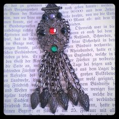 "Vintage gunmetal rhinestone articulated brooch Vintage gunmetal tone brooch pin adorned with red, purple,  green and black rhinestones and 6 articulated danglers. Measures 3.5"" long. Good vintage condition.  The rhinestones were reglued at one point and signs of this show on the back, but is unnoticeable when worn. Vintage Jewelry Brooches"