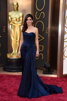 Oscar 2014. Como Amy Adams, Sandra Bullock –nominada como Mejor Actriz por Gravity– ha demostrado que el azuloscurocasinegro es un color hecho para las nominadas al Oscar que quieren experimentar con colores profundos pero prefieren no ir de negro. Este diseño de escultural escote es obra de Sarah Burton para Alexander McQueen.