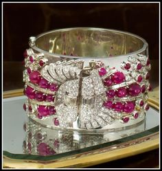 This extremely fabulous Diamond and Ruby cuff bracelet wasn't listed with a date, but the berry-like cabochon Rubies and chunky bow-inspired motif all say midcentury to me. The bracelet itself is a hinged, polished cuff embellished with scrolling Diamond plaques embellished with star Ruby cabochons, both oval and round. The stones are mounted in Platinum and palladium and the Diamonds total 10 carats.