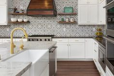 Stunning gray and white transitional kitchen is clad Cement Tile Shop Bordeaux III backsplash tiles that draw your eyes to a stained oak hood mounted between stacked floating wooden shelves above a stainless steel cooktop.