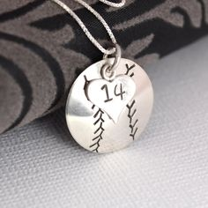 Perfect for a baseball fan or player, this pendant is a 3/4 inch circle hand-stamped and domed to become a baseball. A small heart charm rests on top of it with the players number.