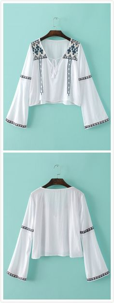 The blouse is featuring v neck with tasseled strings, pullover styling, long flare sleeve and embroidery decoration.