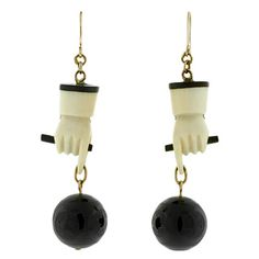 Circa 1850, each earring consists of a hand-carved ivory fist, holding a baton. Dangling from each outstretched thumb and forefinger is a finely carved solid onyx ball, engraved with a pattern of rings and stars.