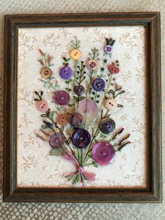 Handsewn framed picture using Antique Buttons as flowers with embroidered stems and leaves then embelished with beads as buds. Stretched on acid-free foamcore and framed in wood. The back is covered with old paper a sawtooth hanger. Measuring 6.5high x 5.5wide and .5deep.