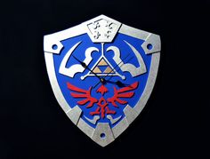 Wood wall clock with of Legend of Zelda Hylian shield.  This wall clock is made and painted entirely by hand.  It is made of wood 3 mm thick.