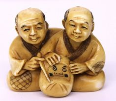 """19th C. Japanese Carved Ivory Netsuke, two men holding mask. Measures - 1 1/2"""" high x 1 3/4"""" wide."""