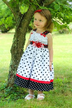 Our little girls Minnie summer dress, with red satin ribbons on the shoulder straps that end in little red bows.  A master piece! Runs true to size. Recommended for Birthday Portraits, Disney trips or cruise. Coordinated and matching sister dresses for family pictures.  http://www.carouselwear.com/girls-little-girls-minnie-ruffled-polka-dot-dress.html