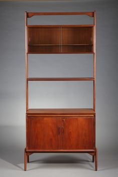 Teak modular bookcase composed of a shelf and two containers: an upper container with glass sliding doors and a small shelf inside, and a low container with two practical storage compartments and two small drawers for documents. They are surmounted by a large flap. Danish work of the 70s.
