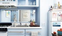 Powder blue kitchen with open shelving and sleek silver hardware.