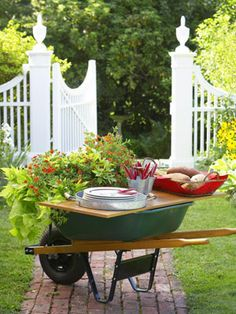 Topped with shelving planks, a wheelbarrow becomes a moveable  sideboard for plates and cutlery for outdoor parties!!
