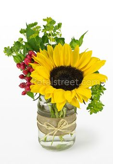 Sunflower and red berries in a mason jar.