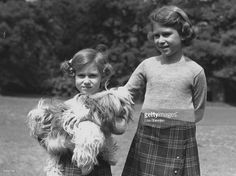 Queen Elizabeth II (as Princess Elizabeth) and her younger sister Princess Margaret (1930 - 2002) in the grounds of the Royal Lodge, Windsor. Princess Margaret is holding one of their pet dogs, a Cairngorm terrier called Chu-Chu.