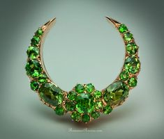 """A Superb Antique Russian Demantoid Garnet Brooch Pin circa 1885 of a crescent shape, centered with a cluster (central stone approximately 0.70 ct), flanked by two large oval demantoids (approximately 1.15 ct and 1.04 ct),   all stones have """"horsetail"""" inclusions typical for Russian Uralian demantoids, approximate combined demantoid weight - 5.24 ct."""