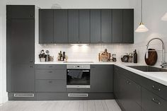 This dark grey kitchen contrasts so nicely against the white tile backsplash. Combined with some wood chopping board and a touch of copper from the Menu water jug, it really makes a very inviting kitchen. Grey Kitchen Designs, Kitchen Room Design, Modern Kitchen Design, Kitchen Interior, Grey Kitchen Furniture, Modern Kitchen Cabinets, Dark Grey Kitchen Cabinets, Kitchen Walls, Kitchen Countertops