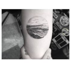 Fine line style landscape circle tattoo on the forearm.