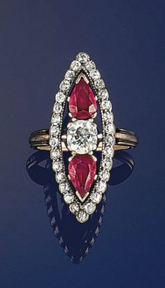 A 19th century ruby and diamond ring  The cushion shaped old brilliant-cut diamond between pear shaped ruby sngle stones with old-cut diamond marquise shaped border, mounted in silver and gold