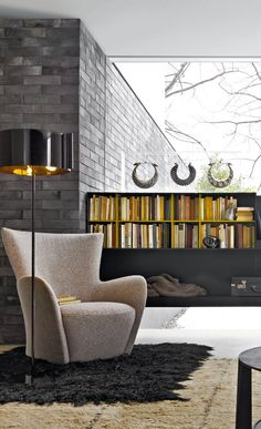 Mandrague lounge chair in soft dove gray, black shade with gold floor lamp with sleek & low shelving cabinetry.