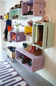 Shoes organized in old, painted crates, nailed to the wall (in lieu of closet space?)