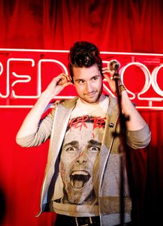 Dan Smith of Bastille, with his face tilted and his gray hoodie