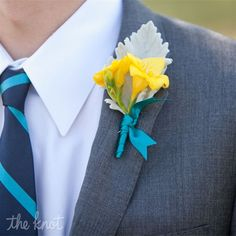 The fathers will wear boutonnieres of yellow freesia and grey dusty miller wrapped in grey ribbon with the stems showing.