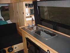 Beautiful cabinetry in Nate's DIY Sprinter DIY conversion. Also a clever location for his solar system monitor and heating controls above the galley area.