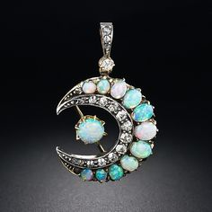 antique crescent pendant crafted in silver over gold, aglow with very fine small opals displaying every color of the rainbow. A twinkling of old mine-cut diamonds completes this splendid antique piece