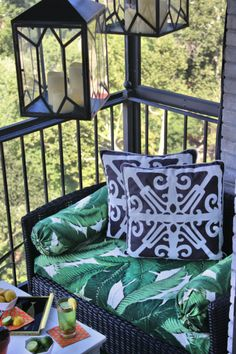 REVEAL // Viceroy Inspired Balcony Outdoor lanterns, outdoor love seats, green black and white stripe bamboo pattern outdoor throw pillows, outdoor ottoman, banana palm leaf print outdoor fabric, vintage brass pitcher, vintage cocktail glasses, HGTV Star, DIY, aloe plants, astro turf, high-rise pre-war, apartment building patio balcony terrace, outdoor entertaining, orange gold polka dot cocktail napkin, vintage equestrian ashtray, black and gold tray