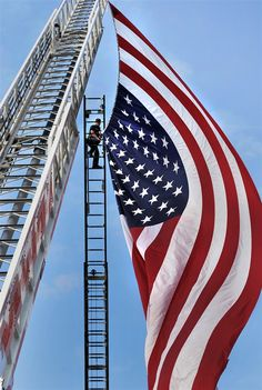 """Ed Lawrence, a firefighter in Wheeling, W.V., helps hang a giant 40 foot long American Flag from two ladder trucks during an """"Honor Our Troops"""" event as part of a 4th of July weekend celebration honoring U.S. troops."""