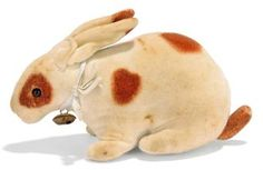 A STEIFF VELVET RATTLE RABBIT, (3410), white with brown spots, black boot button eyes, pink stitching and ribbon with bell, circa 1905 --4½in. (11.5cm.) long (some stain spotting)