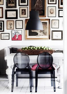 Dining room gallery wall with black ghost chairs.