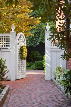 White fence, gorgeous gate, and brick walkway ~ welcoming