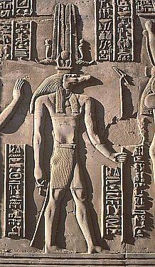 """Sobek, se le representaba con cuerpo humano y cabeza de cocodrilo.Sobre ésta lleva unos cuernos retorcidos de los que salen dos plumas, un disco solar y dos ureos. Al parecer, el Nilo surgió del sudor de Sobek, pues este dios fue su creador. Era llamado """"Señor de las aguas"""". Sobek era adorado para favorecer la fertilidad y la abundancia, y para alejar el peligro de los cocodrilos del Nilo."""