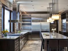 Kitchen With Industrial Flair    Professional-grade appliances and an efficient layout make this kitchen worthy of a restaurant. Stone walls and floors balance the stainless steel elements and keep the space from feeling cold. Design by Tina Muller