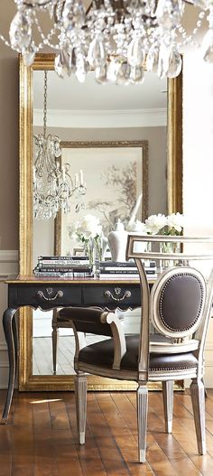 Gorgeous gold hues with black table and black fabric on the chair. Lovely gold mirror and stunning chandelier.